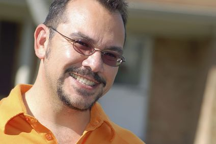 A man wearing an orange polo shirt with orange sunglasses