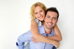 Smiling man and woman on white background.