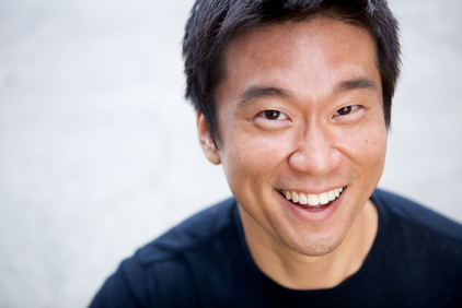 A smiling man in his 20s or 30s wearing a simple black t-shirt