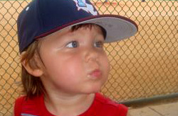 Toddler boy wearing baseball cap looking off camera