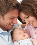Close shot of young couple smiling down at sleeping infant